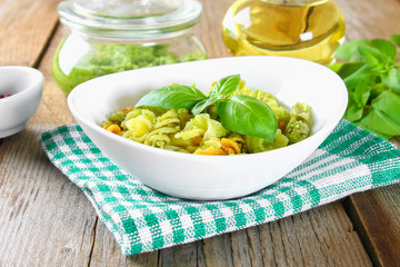 Pasta with pesto sauce on an old wooden table.