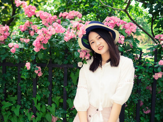 Outdoor portrait of beautiful young Chinese woman in casual dress smiling among pink rose flowers wall in spring garden.