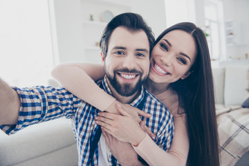 Self portrait of funny foolish couple in casual outfits bearded man carrying his lover on back shooting selfie on front camera indoor