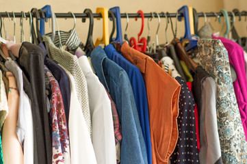 Fashion clothes on clothing rack. Closeup of rainbow color choice of trendy wear on hangers in store closet or spring cleaning concept. Clothes hang on a shelf in a clothes store
