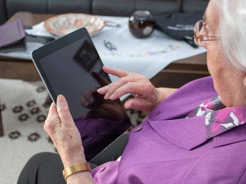 95-jährige Frau sitzt im Wohnzimmer und tippt auf einem mobilen Gerät oder iPad