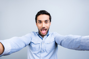 Self portrait of funny comic guy with black hair gesturing tongue out shooting selfie with two hands on front camera isolated on grey background