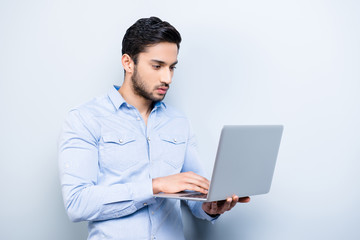 Portrait of attractive hardworking person with black hair texting on keypad keyboard using wi-fi internet on laptop checking email making blog online shopping isolated on grey background