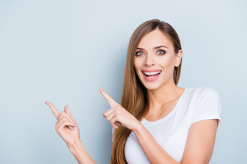 Portrait of positive funny girl in white t-shirt pointing two forefingers to copy space empty place isolated on grey background looking at camera