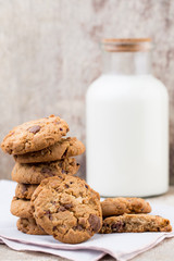 Chocolate oatmeal chip cookies with milk on the rustic wooden table.