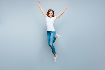 Portrait of active positive girl jumping with hands up raised leg isolated on grey background looking at camera enjoying summer time