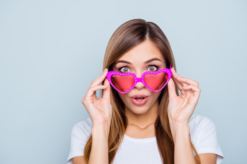 Portrait of shocked frustrated girl looking out pink glasses in heart shape with wide open eyes mouth isolated on grey background