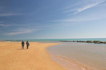 Two elderly ladies having a friendly walk on the beach