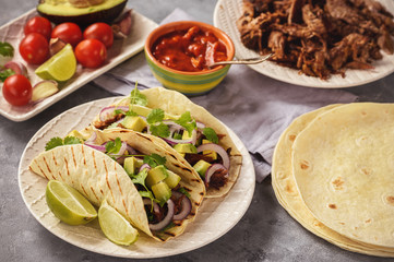 Pulled porc carnitas with avocado and red onion on tortillas. mexican food.