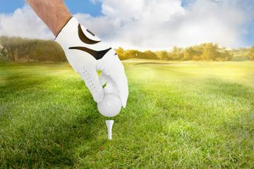 Golfer legt Golfball auf das tee für den Abschlag