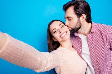 Self portrait of attractive lovely couple, man with stubble kissing in cheek lover shooting selfie on front camera, celebrating 14-february, isolated on bright blue background
