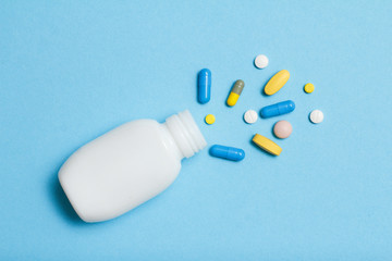 White bottle with different pills and capsules on blue background