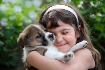 Tierliebe: Kleines Nädchen kuschelt mit Hund Welpe American Akita Mix