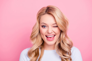 Portrait of funny foolish girl with modern hairdo winking with one eye open mouth, playing with lover isolated on pink background