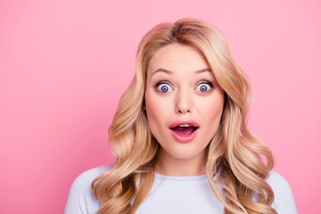 Sale! Portrait of shocked wondered girl with modern hairdo and wide open mouth eyes looking at camera isolated on pink background