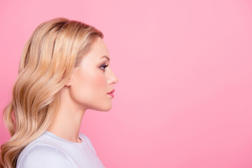 Profile side view portrait with copyspace empty place for product of  serious concentrated girl with modern hairdo isolated on pink background. Advertisement concept