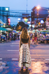 Thailand, Bangkok, young woman in the city standing on the street at night