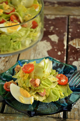Chicken salad with cherry tomatoes on wooden background