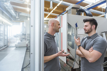Two men discussing at machine in modern factory
