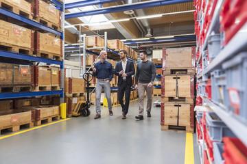 Three men walking and talking in factory storeroom