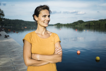 Portrait of smiling woman standing on jetty at a lake
