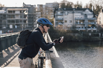 Senior man with cyclist helmet using smartphone on bridge