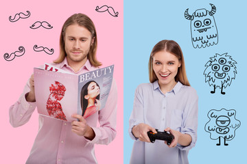 Active and passive. Close up of young positive couple playing video games and reading magazine while standing against colored background
