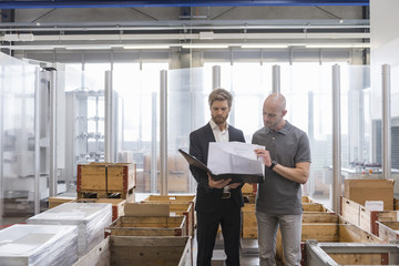 Businessman and employee looking at plan in factory storeroom