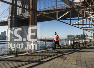 USA, New York City, man running at East River with data emerging from smartwatch