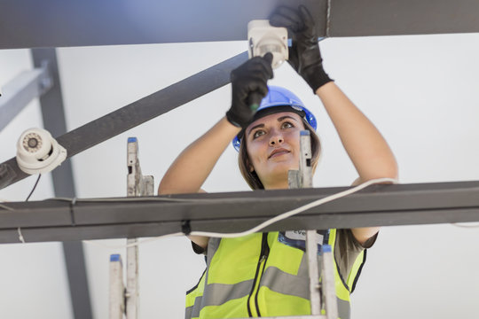 Young female electrician installing lamp