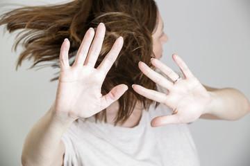 Self defense, studio portrait of scared woman raising hands up in defense
