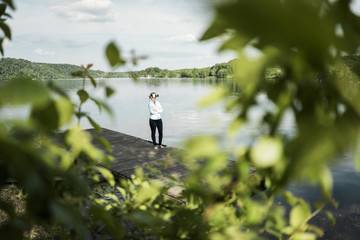 Woman standing on jetty at a lake wearing VR glasses