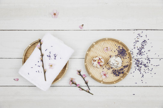Blossom soap balls on bamboo bowl with towel, cherry and lavender blossom
