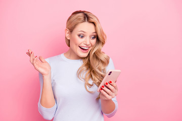 Portrait of wondered woman, excited student, shocked girlfriend having smart phone cellphone in hands watching picture video reading news isolated on pink background