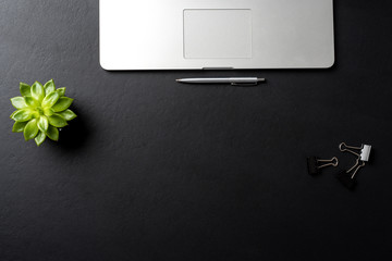 Elegant black office desktop with laptop and accessories. Copy space