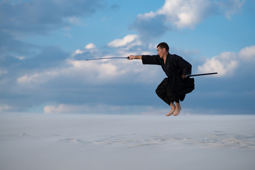 Man jumps during training martial arts in desert