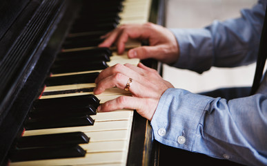 Close-up of male hands playing piano.With wedding ring.