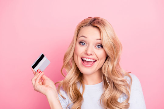 Portrait of cheerful foolish girl with modern curly hair holding credit card in hand going to do online shopping spending a lot of money isolated on pink background