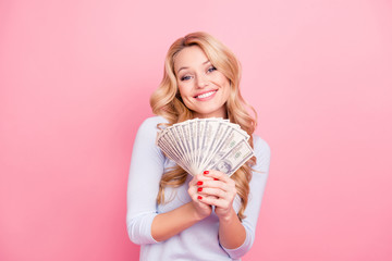 Portrait of cute positive girl in casual outfit holding fan of a lot of, much money for shopping in hands looking at camera, isolated on pink background