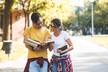 Young student couple going to college class.They walks trough university campus and reading a book.