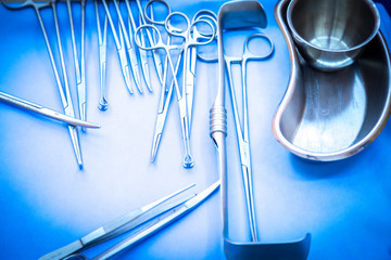 surgical instruments and tools including scalpels, forceps and tweezers arranged on a table for a surgery in surgery room