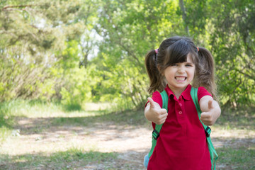 Back to school concept outdoor. Preschool girl with backpack showing thumbs up and looking at camera. Space for advertising, text, or content