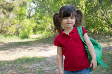 Happy schoolgirl 5 years old enjoy going to school. Back to school and Education concept. She is smiling and keep her backpack. Space for advertising, text, or content