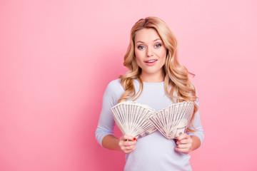 Portrait of cool freelancer carefree girl looking at camera having two fans from much money in hands isolated on pink background
