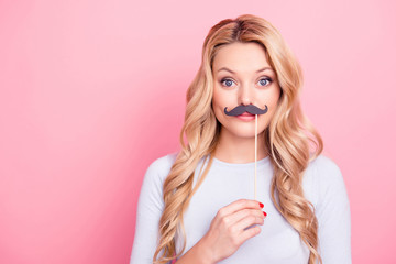 Portrait of funky foolish  big eyed girl holding black carton mustache on stick in hand looking at camera isolated on pink background
