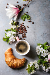 Pink mug of black espresso coffee, french croissant, cream and spring flowers magnolia, blooming cherry branches over grey texture background. Top view, space. Spring greeting card,