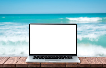 Modern laptop with empty white screen on wooden table against blurred ocean background