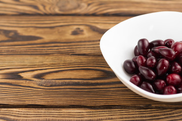 Full white ceramic bowl of red fresh raw dogwood berry on old wooden rustic table with copy space
