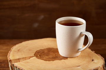 White cup of hot tea on an old log over rustic wooden background, selective focus