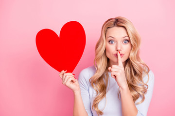 Portrait of funny mysterious girl with curls gesturing silence sign with forefinger holding big red carton heart figure isolated on pink background, celebrating 14-February